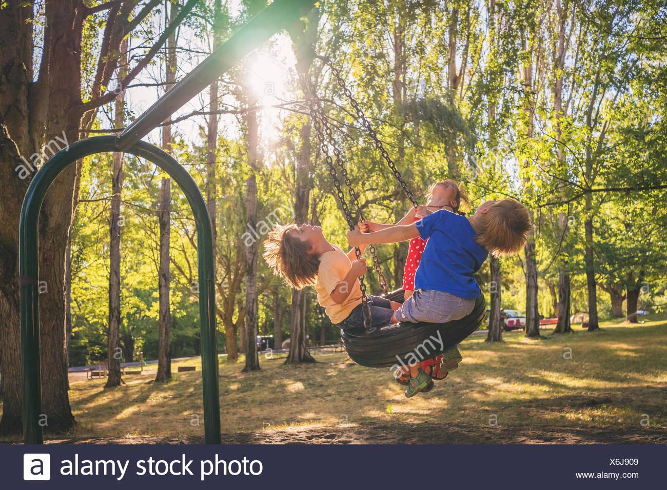 Trois enfants jouant sur une balançoire Photo Stock