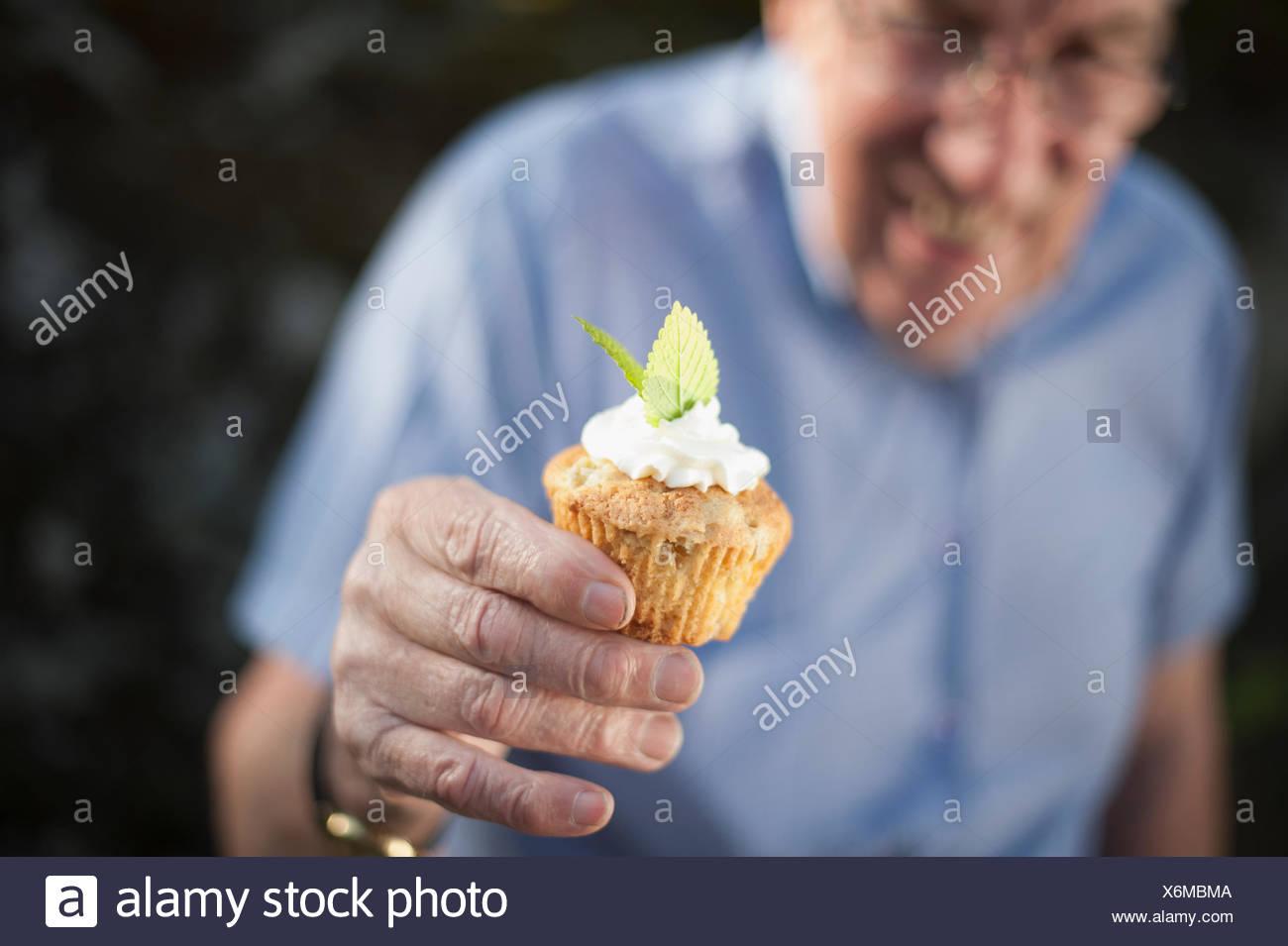 Senior man holding cupcake Photo Stock