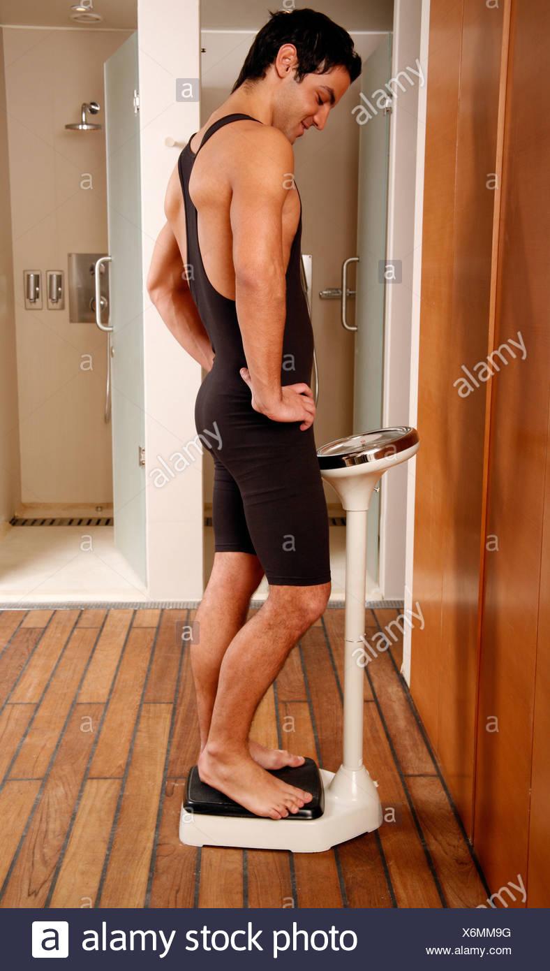 39d5ca107ce2 L homme lui-même sur les balances de pesée dans le vestiaire Banque ...