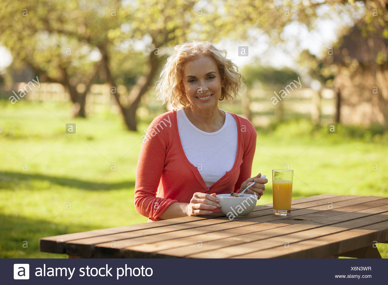 A mature woman sitting at a garden bench eating breakfast Photo Stock