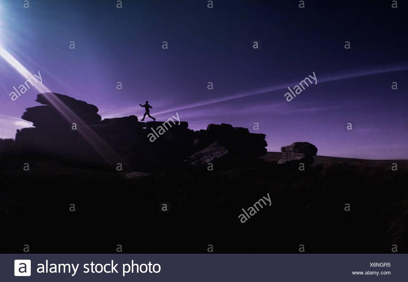 Silhouette personne courant sur les rochers contre Ciel à Dartmoor National Park Photo Stock