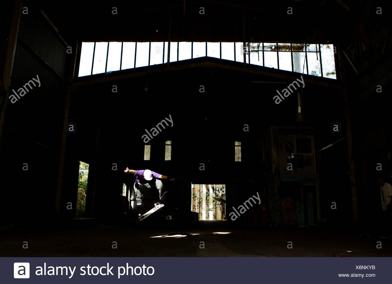 Un patineur exécute un kick flip dans un entrepôt abandonné sur la côte centrale, New South Wales, Australie. Photo Stock