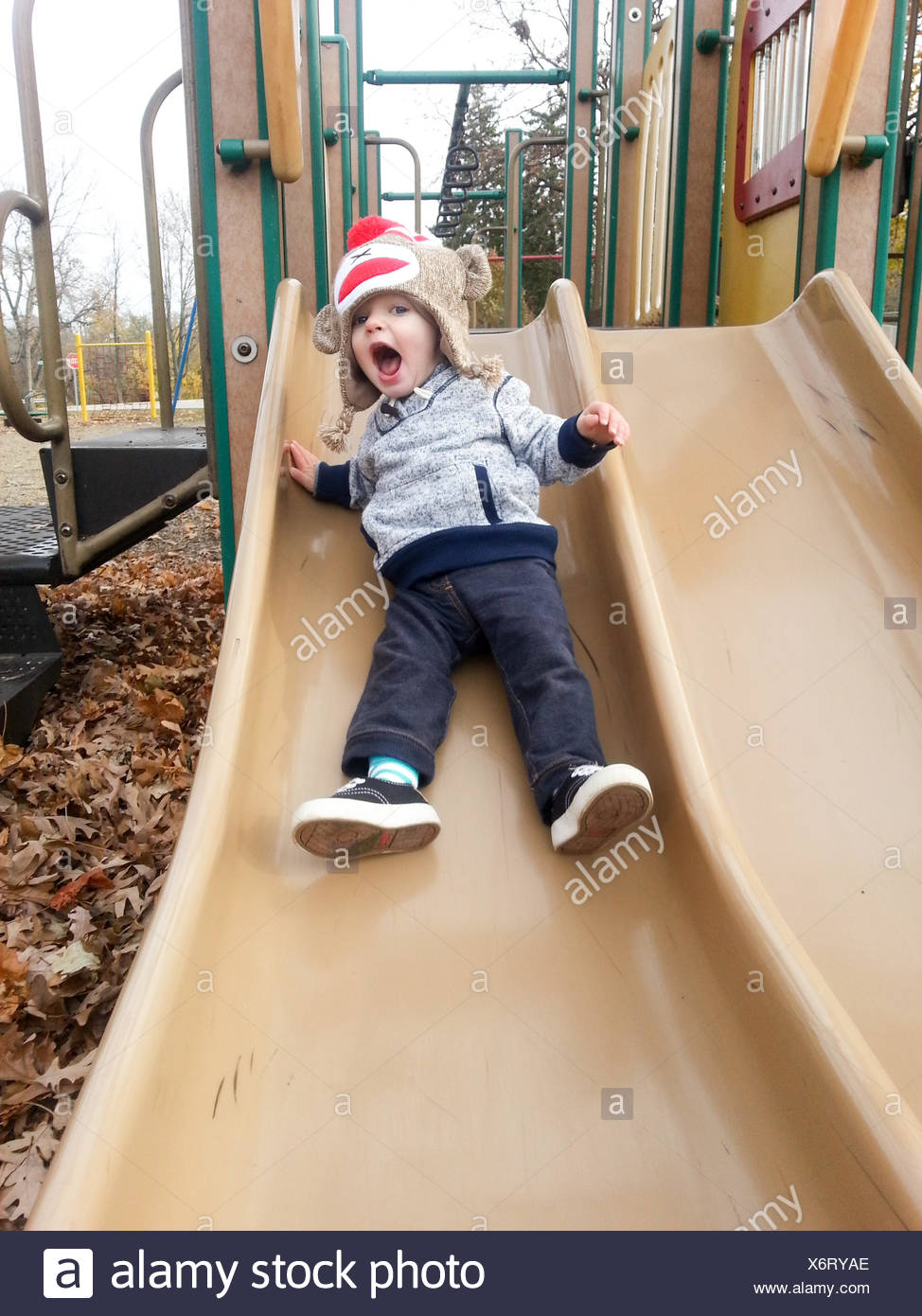 Garçon glisser sur aire Photo Stock