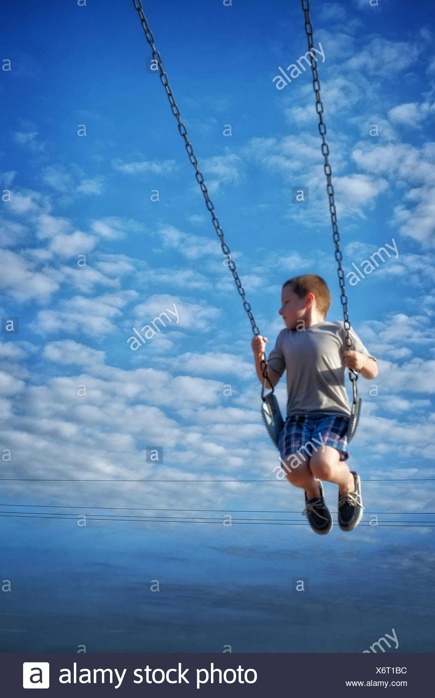 Boy Swinging contre Ciel nuageux Ciel Bleu Photo Stock