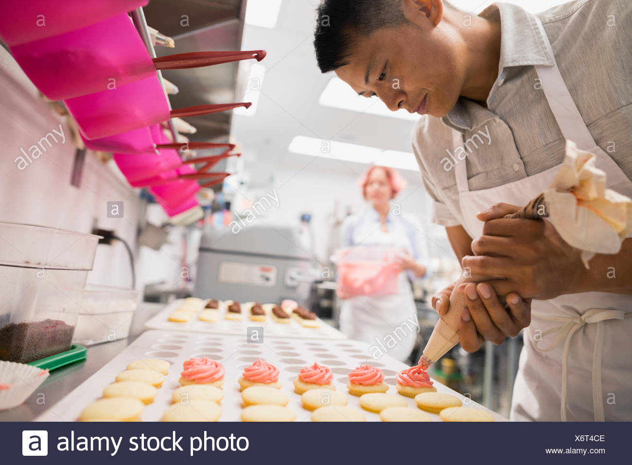 Tuyauterie pâtissier cookies pink icing cuisine commerciale Photo Stock