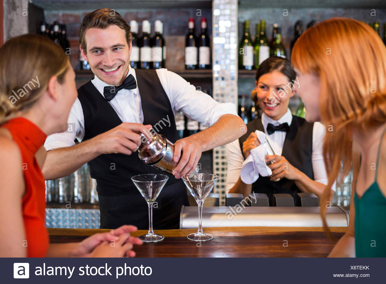 Friends standing au comptoir tout en préparant une boisson barman Photo Stock
