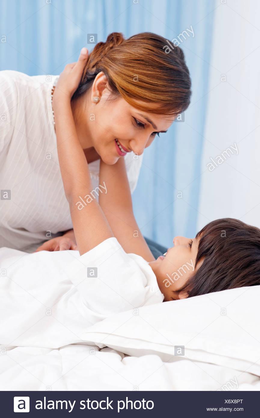 Boy hugging sa mère sur le lit Photo Stock