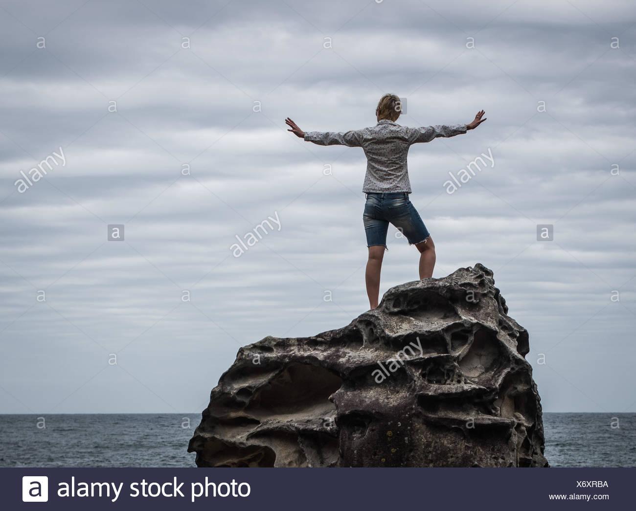 Femme debout à la côte avec ses bras tendus Banque D'Images