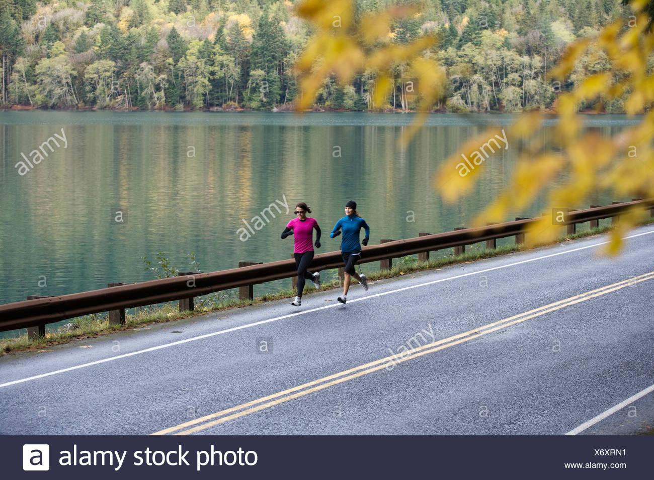 Deux jeunes femmes courent dans le pas sur un jour d'automne par Lake Crescent dans le parc national Olympic. Photo Stock