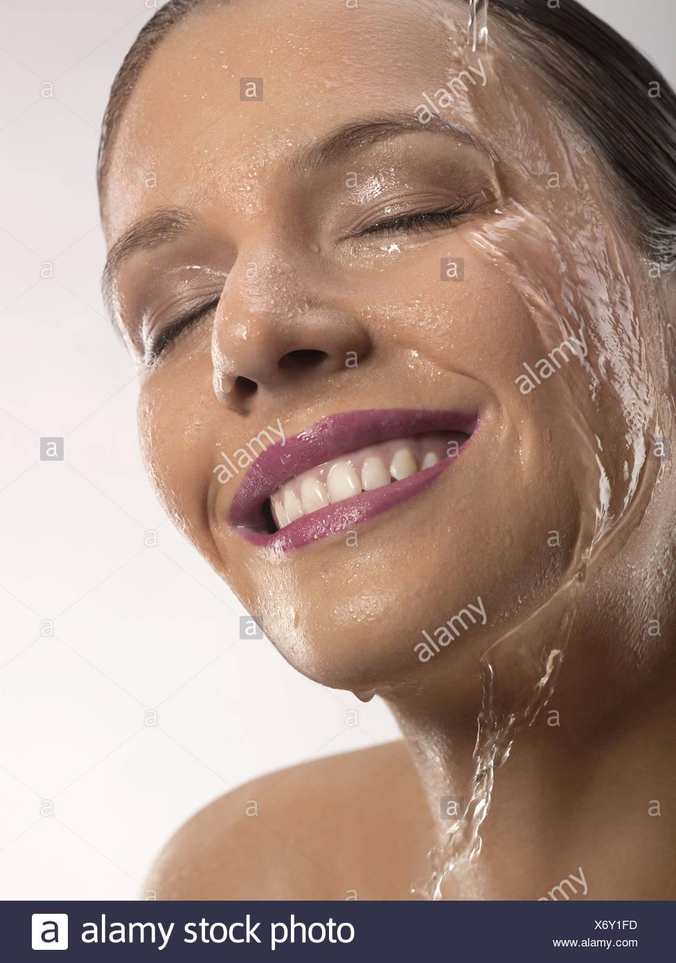 Jeune femme heureuse avec de l'eau en marche sur la tête, studio shot Photo Stock