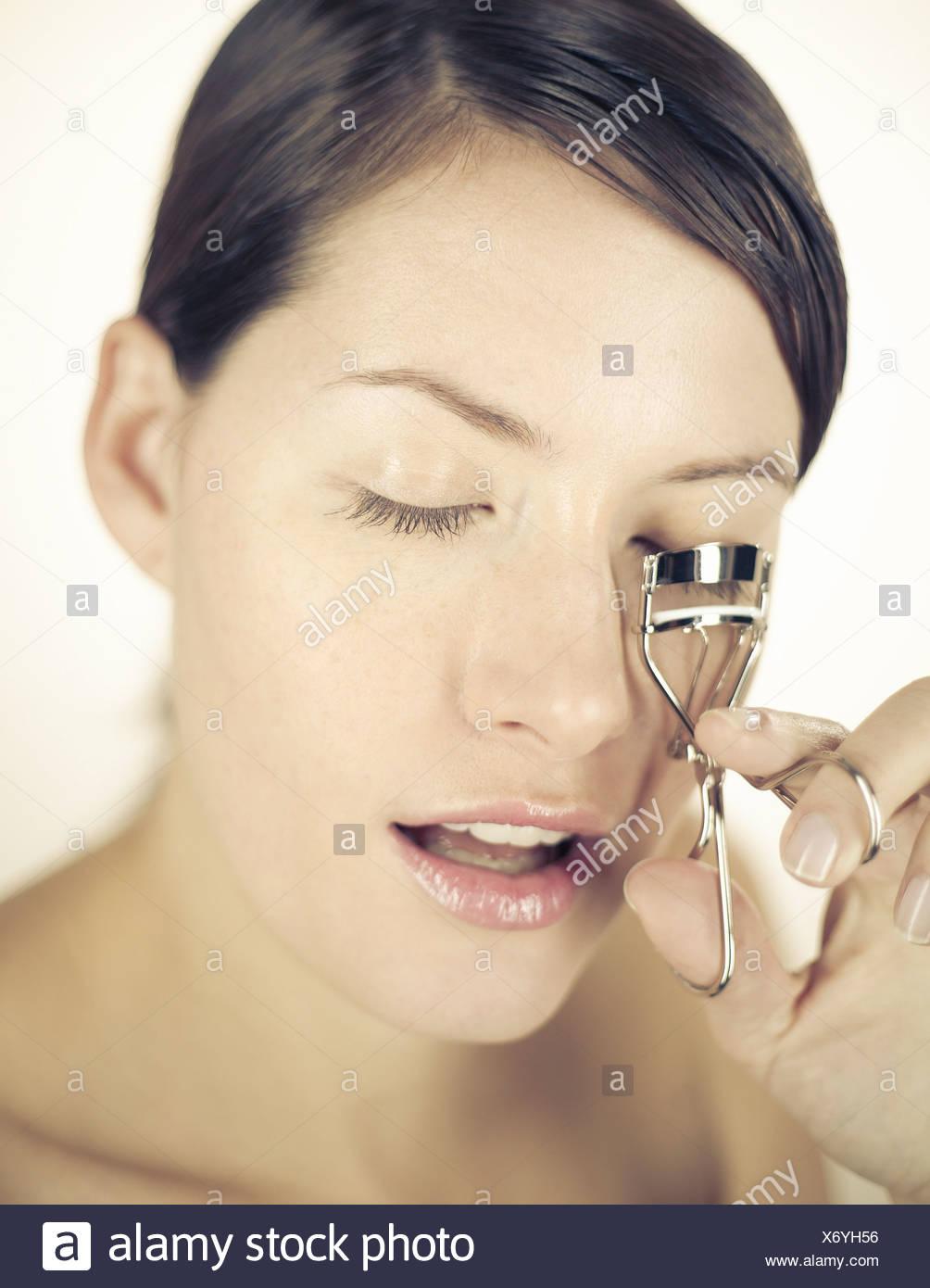 Une jeune femme à l'aide d'eyelash curlers Photo Stock