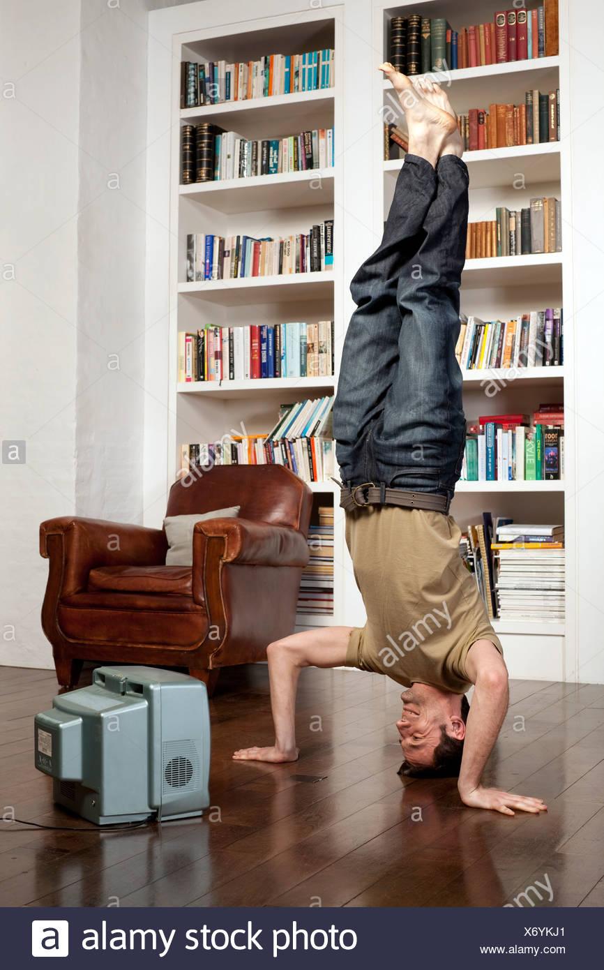 Homme debout sur la tête avec tv Photo Stock
