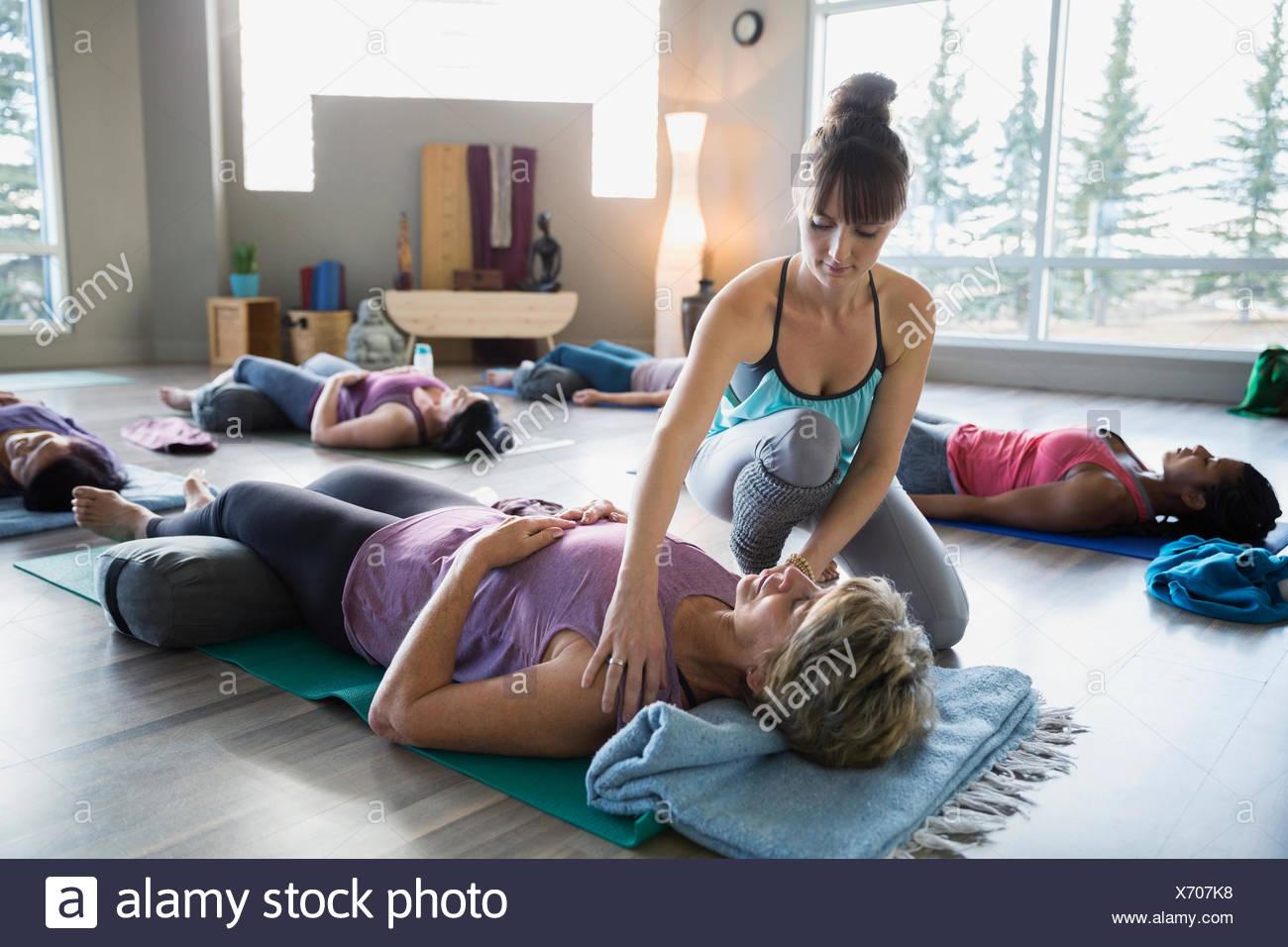 Les étudiants de réglage de l'instructeur de yoga réparatrice dans les épaules Photo Stock