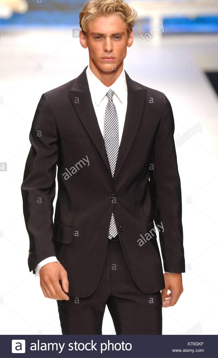 f5c4a03e55a8 Valentino Milan S S de vêtements d homme blond portant un costume noir, la  marche sur la piste blanche