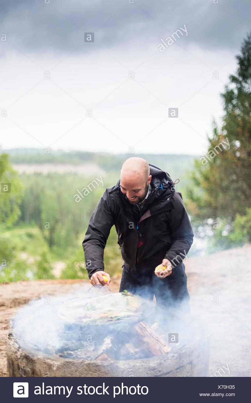 Un homme la cuisson sur un feu de camp Photo Stock