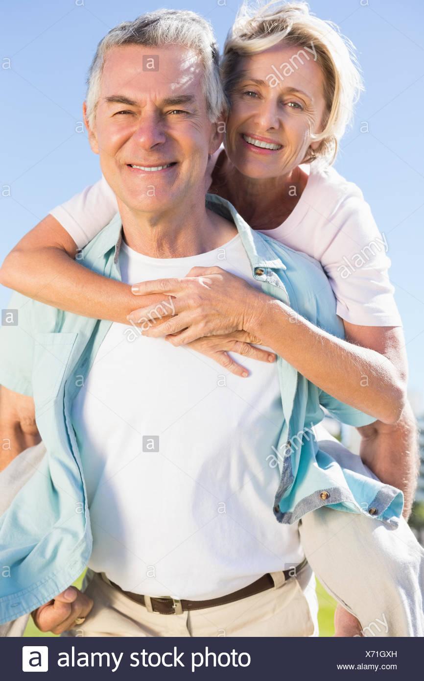 Happy senior man giving son partenaire un piggy back Photo Stock