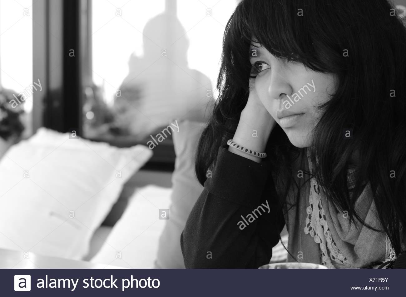 Portrait de femme assise sur un canapé Photo Stock