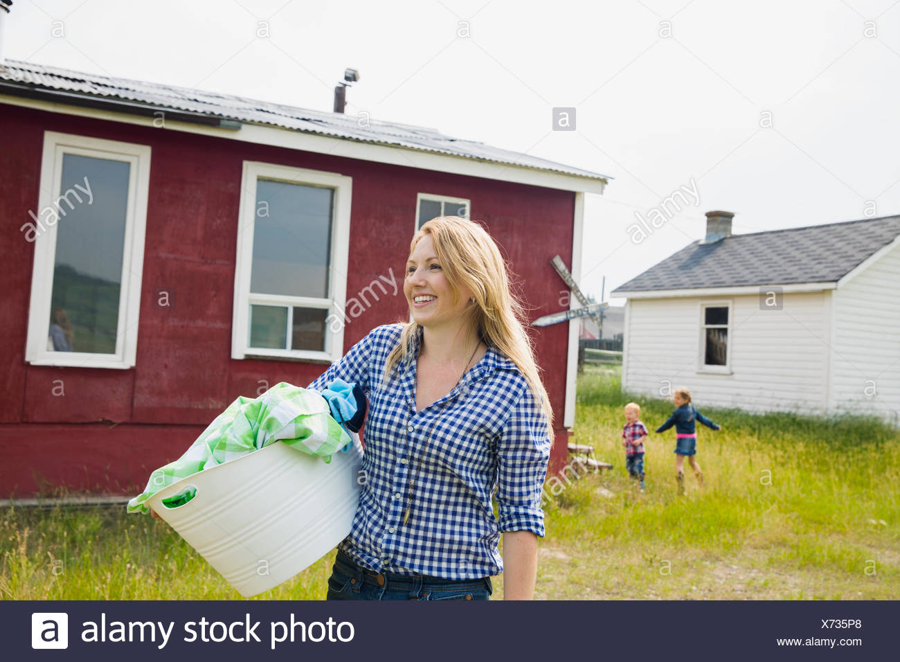 Smiling woman carrying blanchisserie extérieur chambre Photo Stock