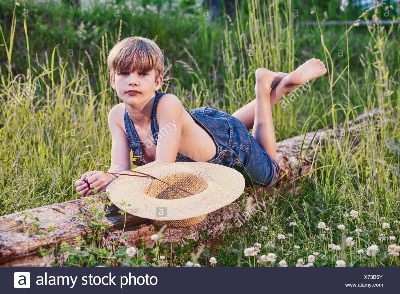 Jeune garçon portant salopette bleue portant sur l'arbre tombé Photo Stock