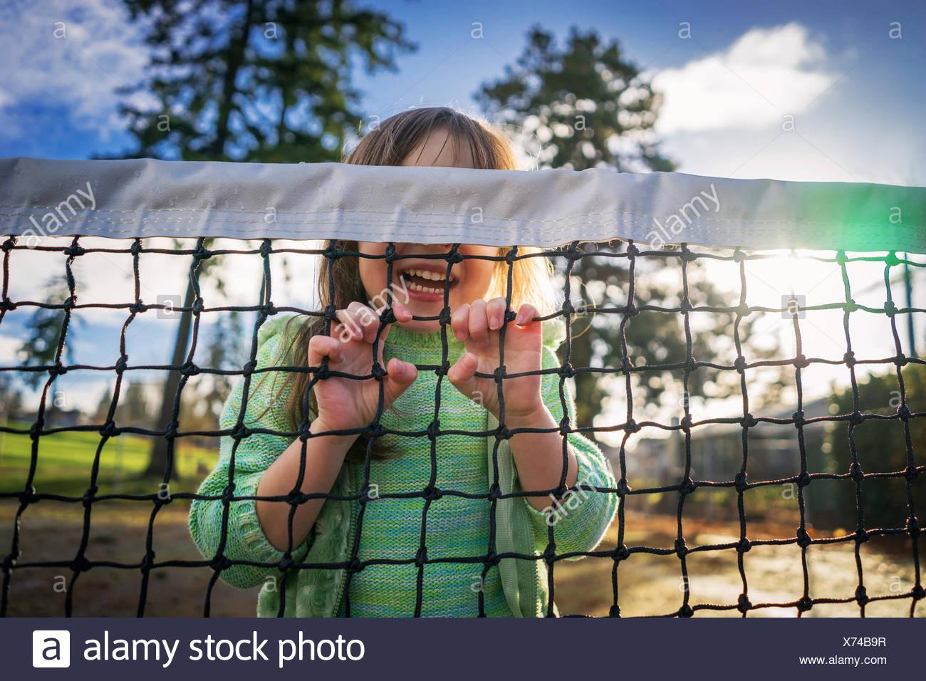 Tennis fille se cacher derrière rire net Banque D'Images