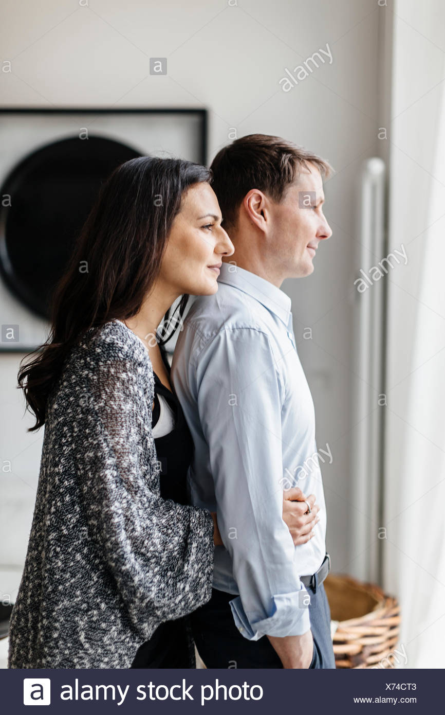 Allemagne, couple hugging in living room Photo Stock
