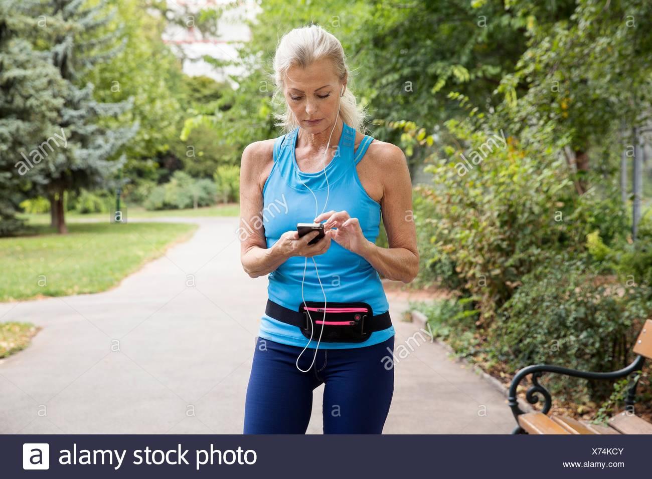 Mature Woman choisir une formation dans la musique tout en smartphone park Photo Stock