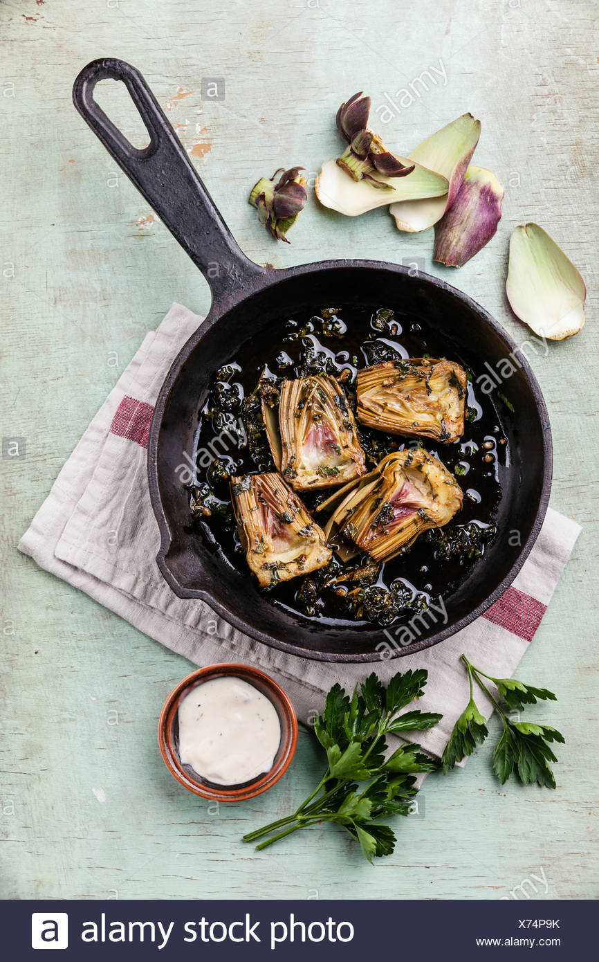Artichauts cuits avec Pan sur fond bleu Photo Stock