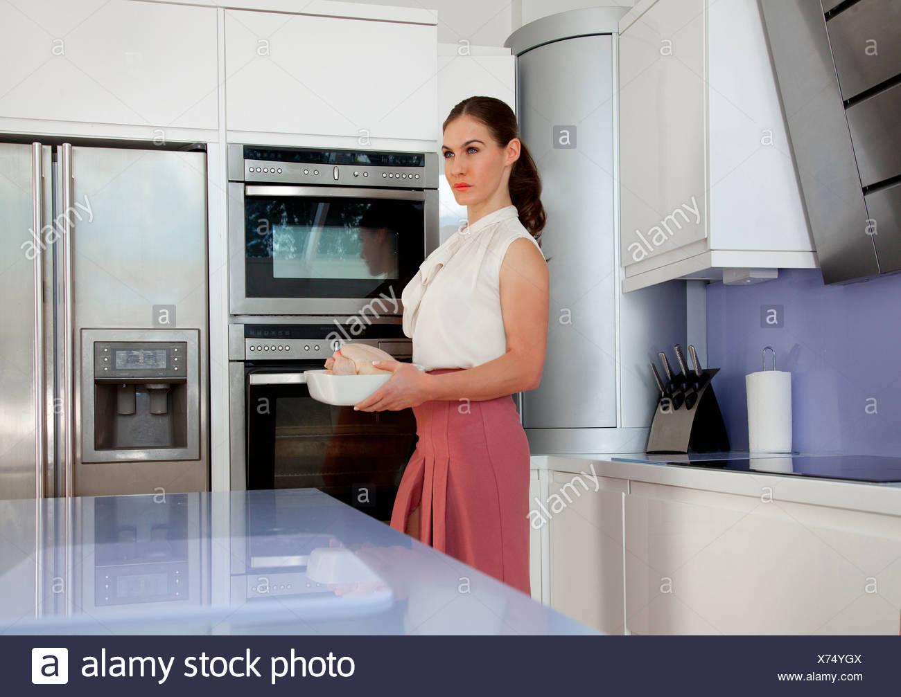 Jeune femme tenant un plat à rôtir dans la cuisine Photo Stock