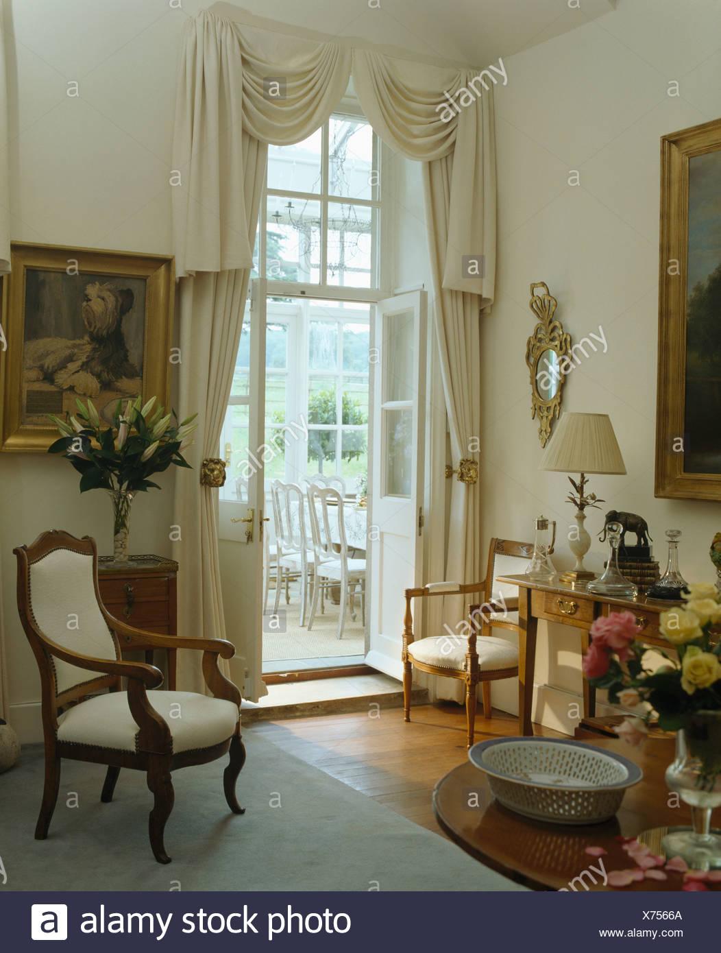 Rideau Pour Porte Fenetre fauteuil recouvert de crème dans le pays avec des rideaux