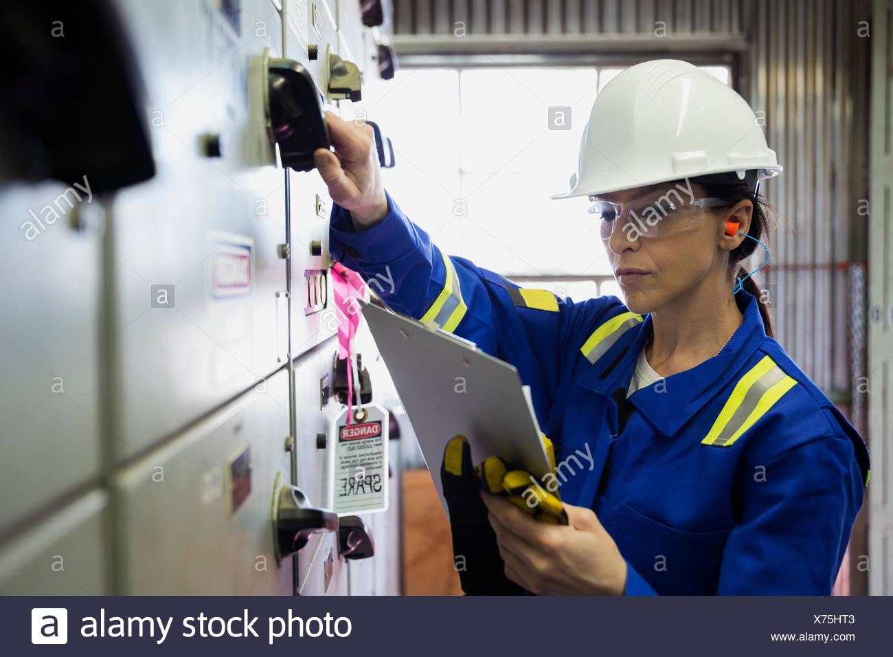 Travailleur féminin au panneau de contrôle en usine à gaz Photo Stock