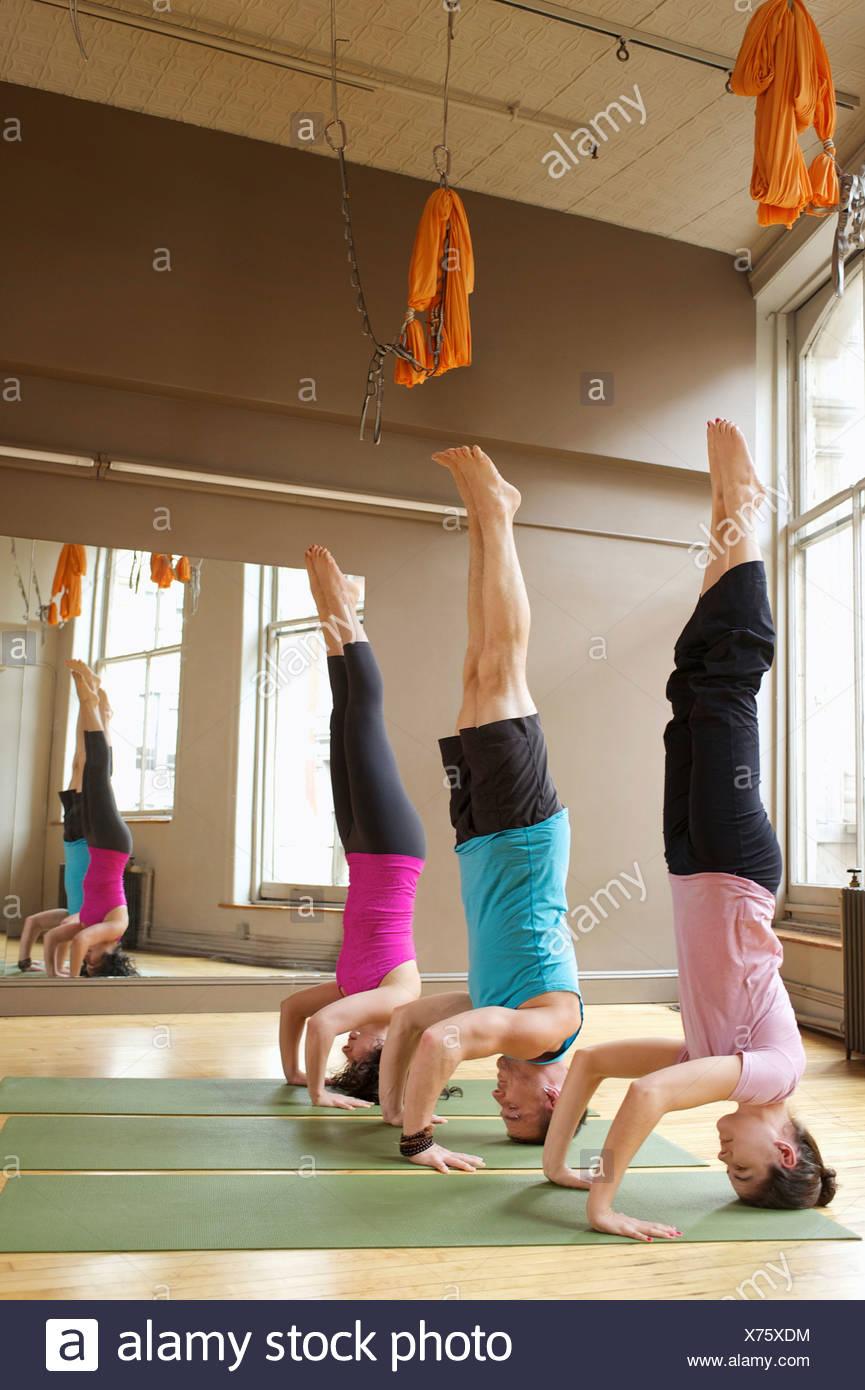 Les gens font (Salamba-Shirshasana headstands) dans la classe de yoga Photo Stock