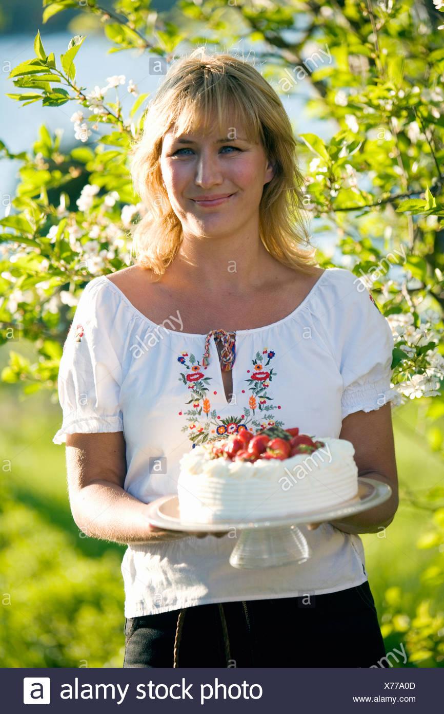 Femme avec un gâteau aux fraises, Fejan, archipel de Stockholm, Suède. Banque D'Images