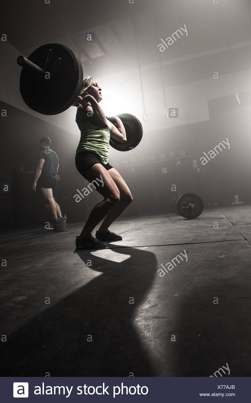Mid adult woman lifting barbell Photo Stock