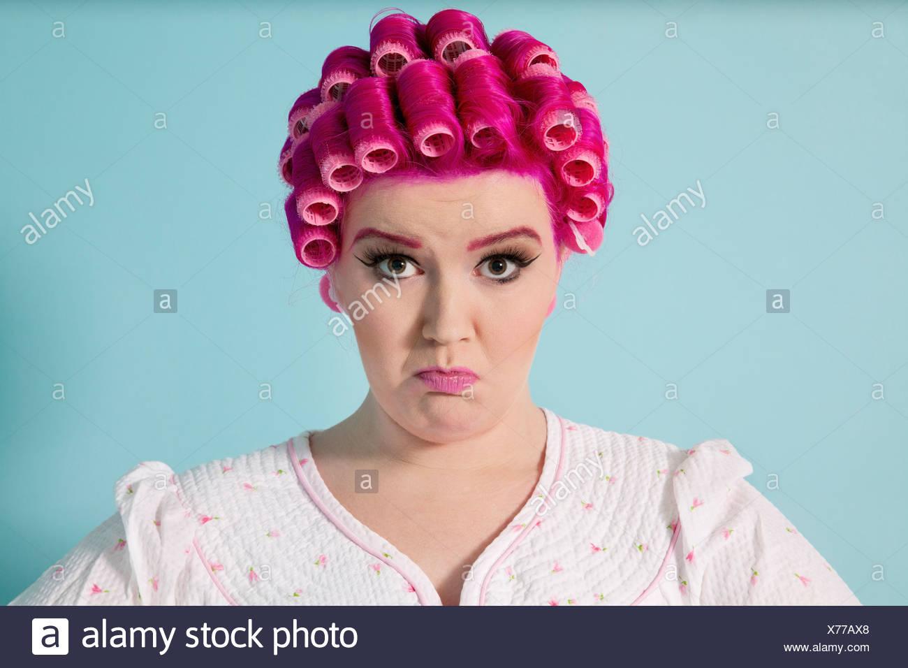 Portrait de jeune femme grimace avec les bigoudis sur fond coloré Photo Stock
