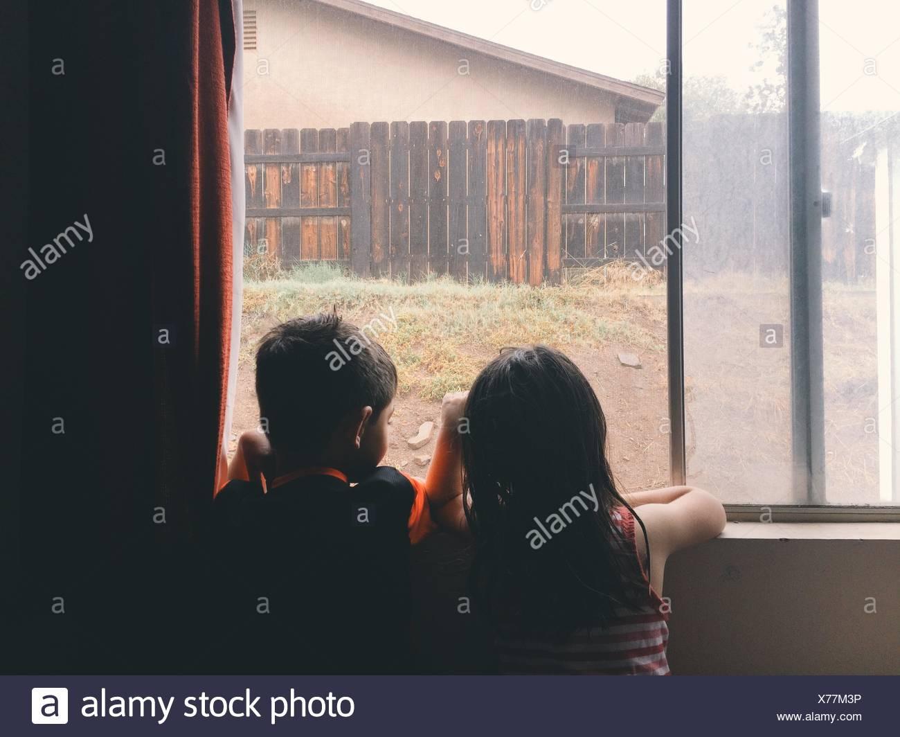 Vue arrière de la fratrie à la fenêtre grâce à à la maison Photo Stock