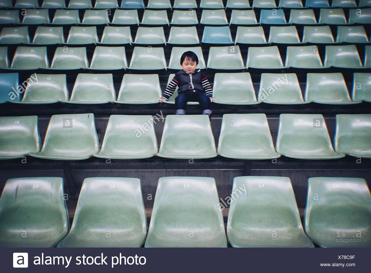 Garçon assis sur une chaise dans le stade Banque D'Images