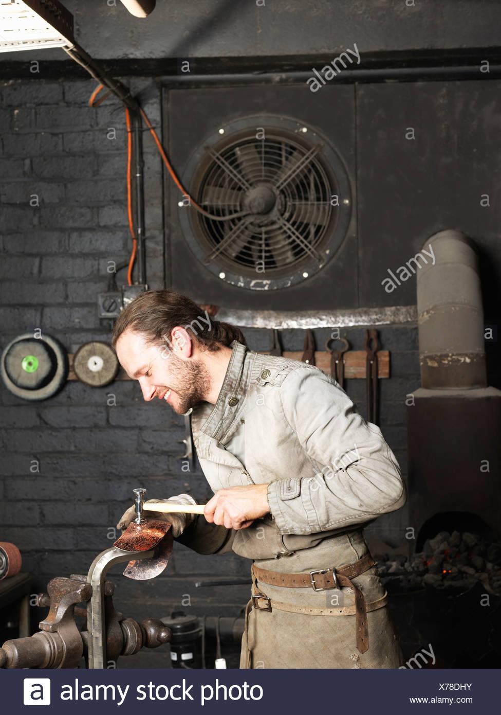 Blacksmith hammering cuivre dans l'atelier Photo Stock