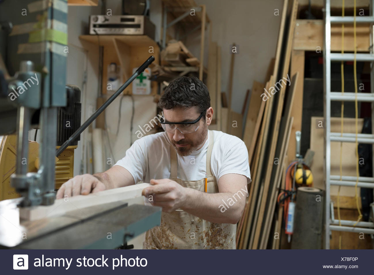 Carpenter en utilisant la perceuse en atelier Photo Stock