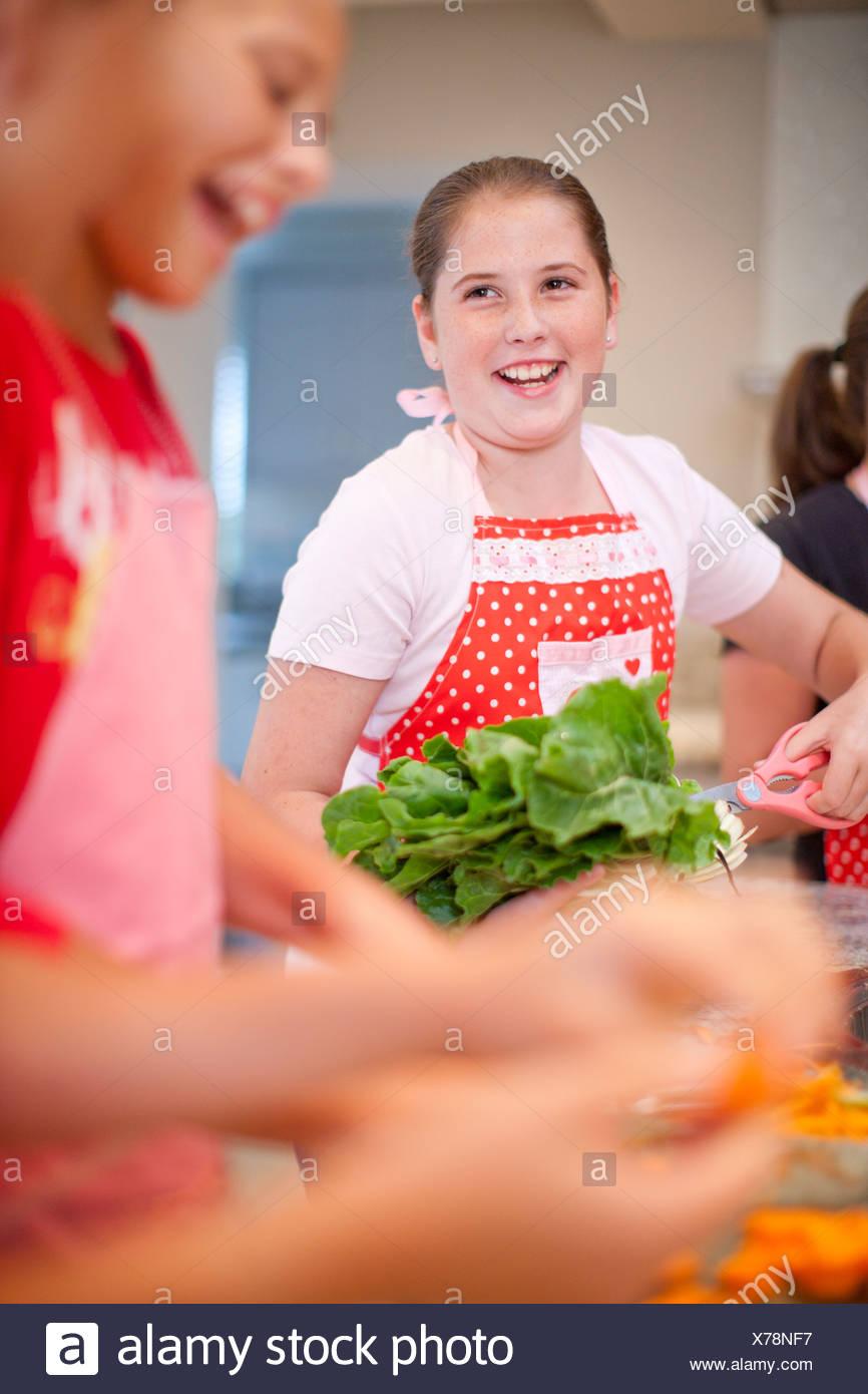 Adolescentes comment préparer les légumes dans la cuisine Photo Stock
