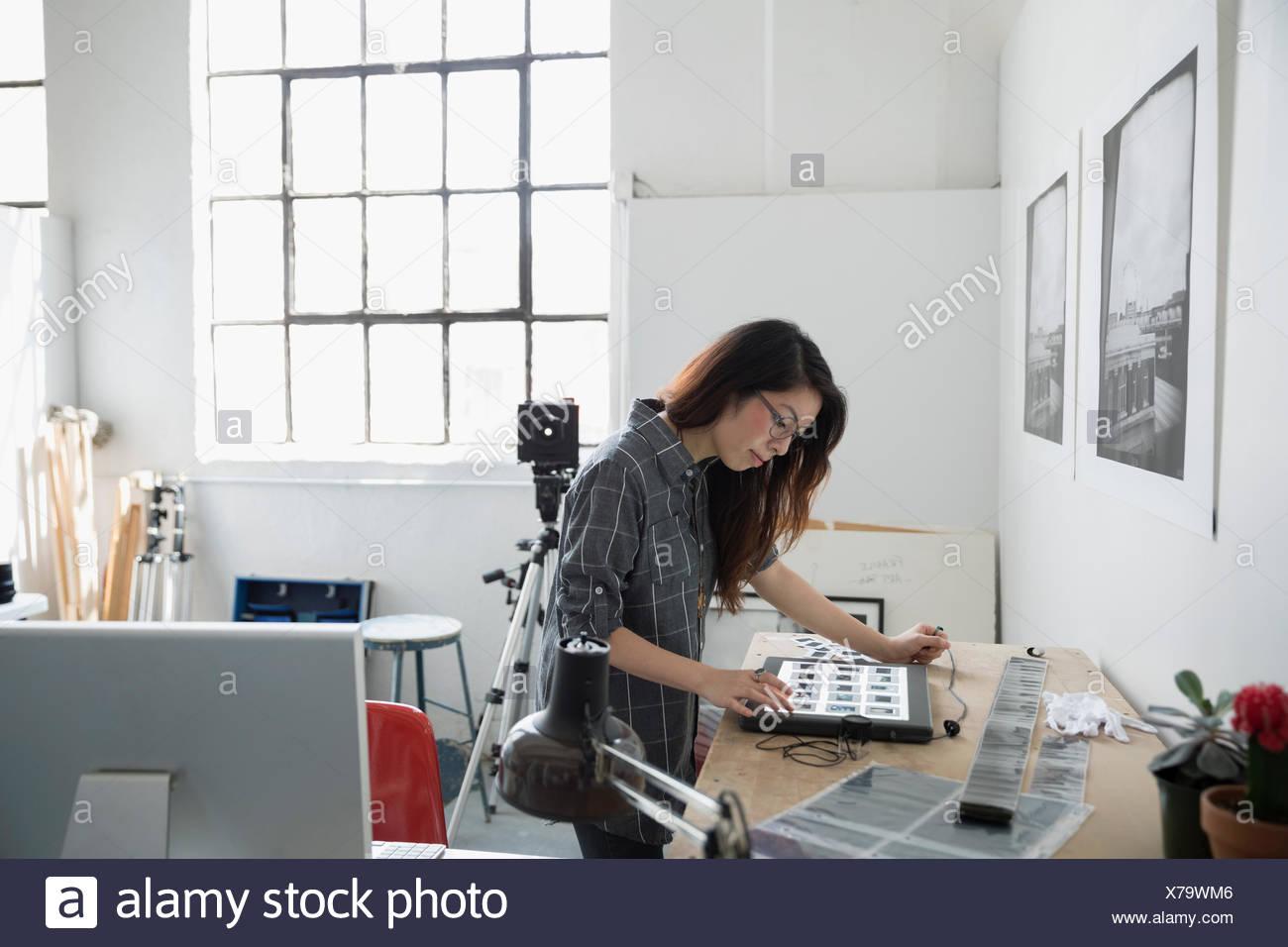 Femme photographe examinant les diapositives en art studio Photo Stock