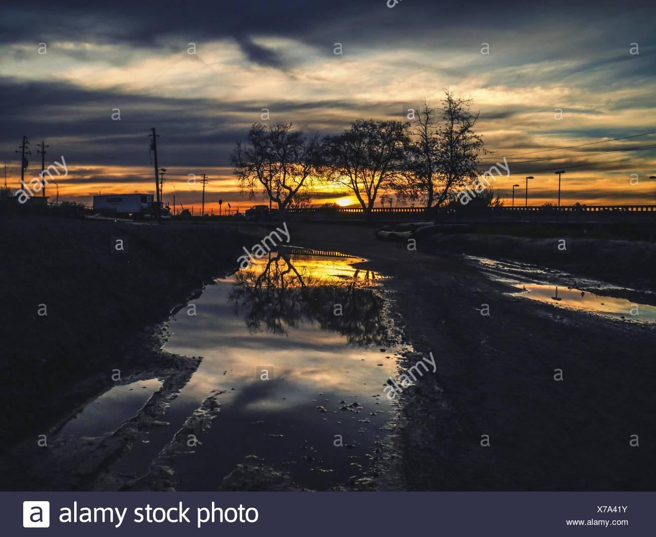 Ciel dramatique qui reflète de flaque en premier plan Photo Stock