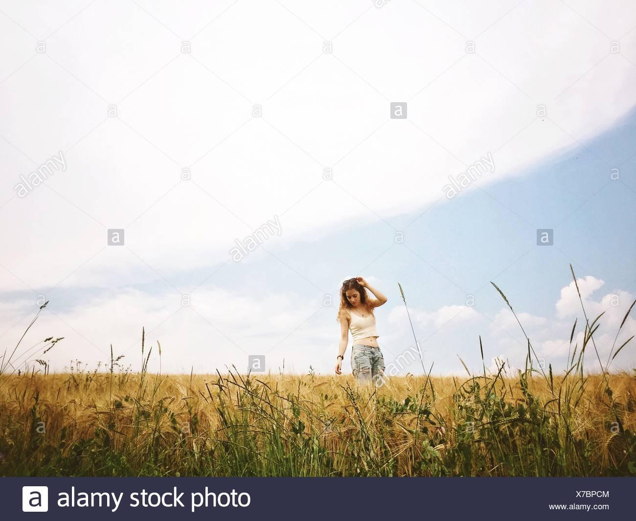 Jeune femme debout sur le champ de blé Photo Stock