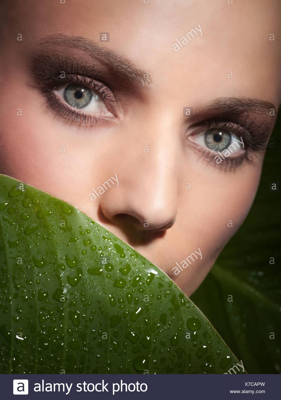 Une jeune femme a' visage derrière une feuille verte Photo Stock