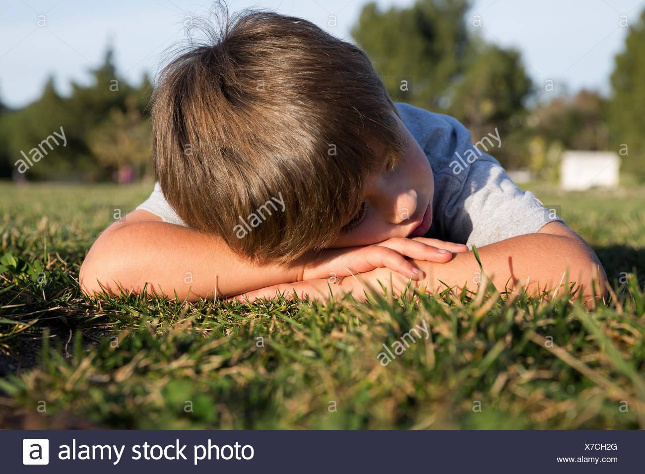Garçon maussade, la tête en bas, couché sur l'herbe du parc Photo Stock