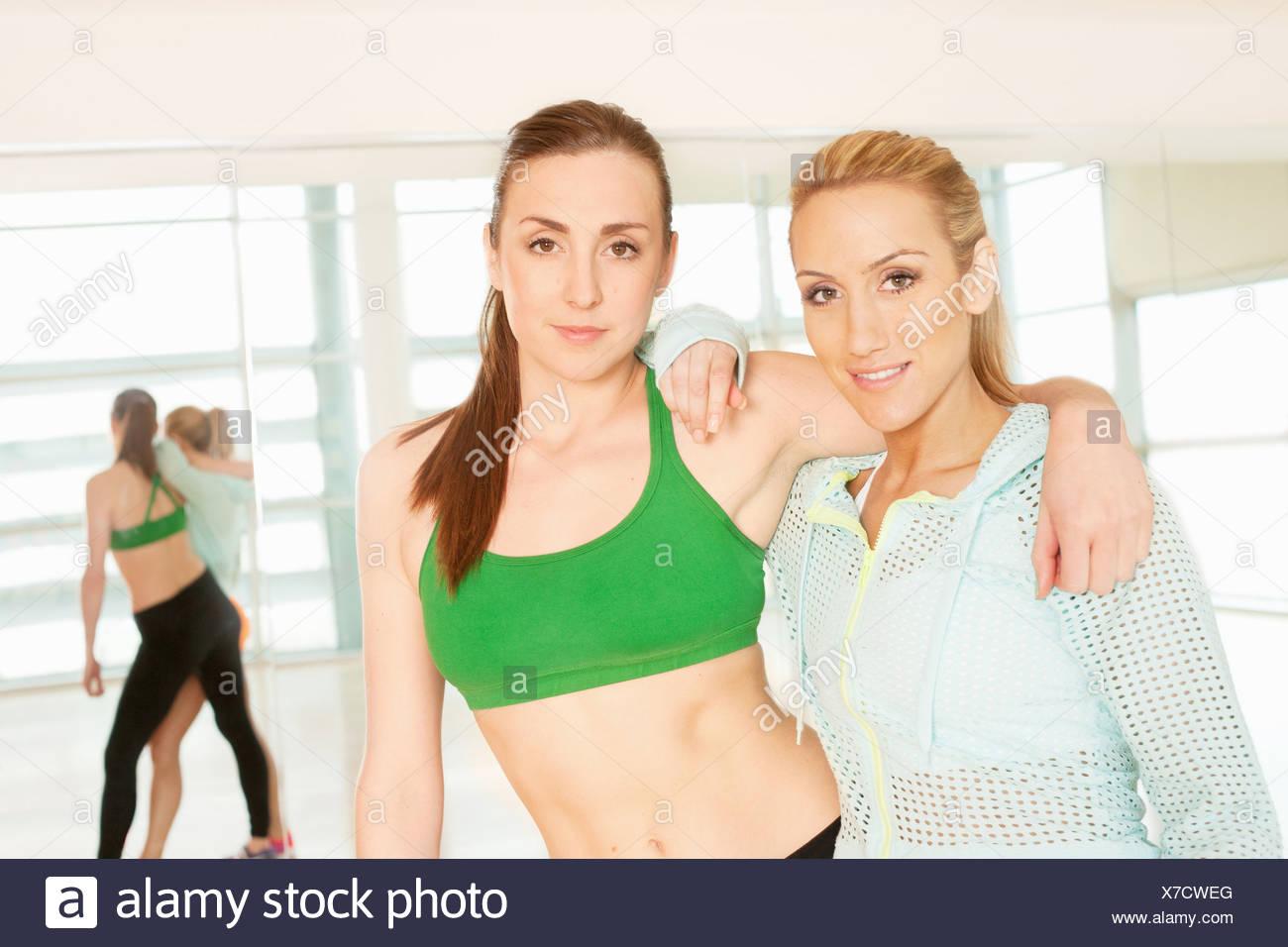La femme debout dans un gymnase avec bras autour de Photo Stock