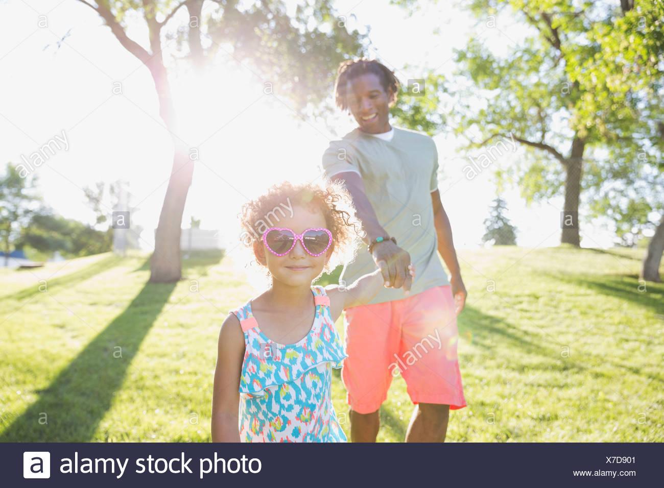Père et fille se tenant la main sur un pied Photo Stock