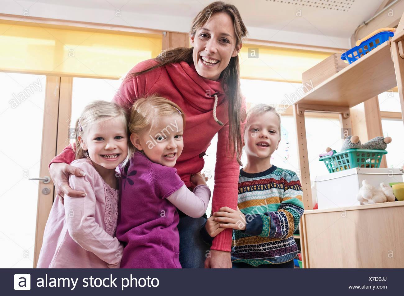 Photo de groupe des femmes d'éducateur et de trois enfants en maternelle Photo Stock