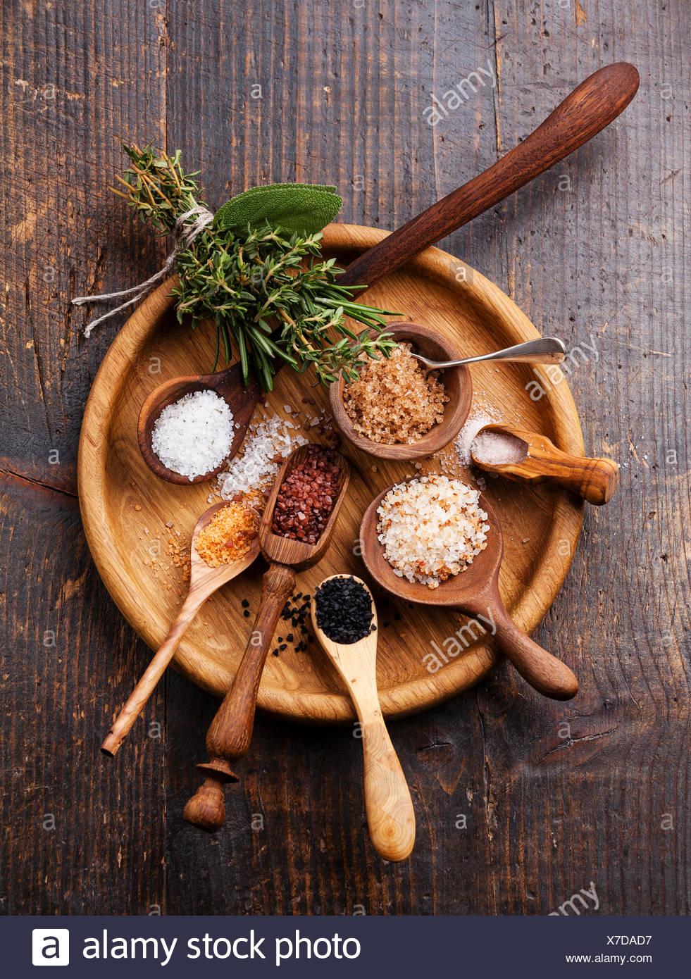 Différents types d'aliments gros sel dans des cuillères en bois sur fond sombre Photo Stock