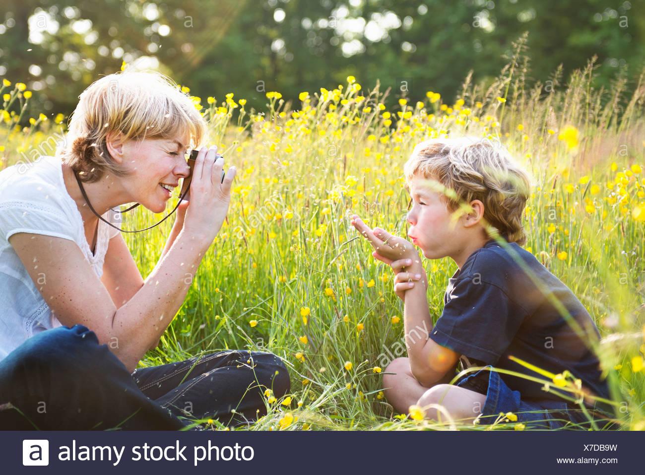 Woman taking photograph of boy blowing kiss Photo Stock