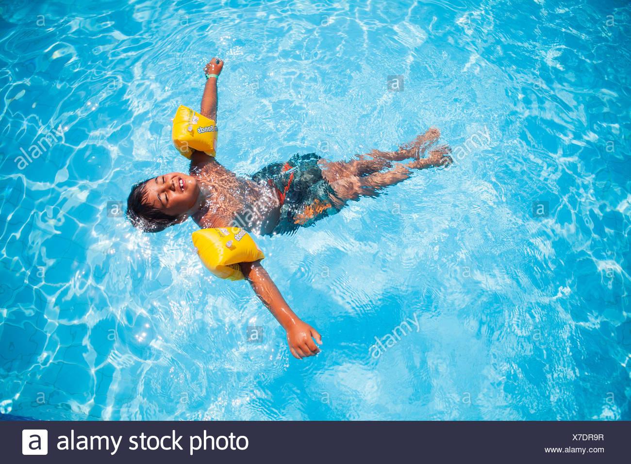 Un garçon portant des ailes de l'eau flottant dans une piscine Photo Stock